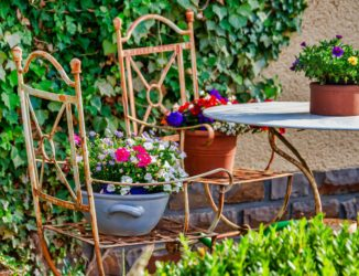 Gartengestaltung mit alten Stühlen und Blumenschalen